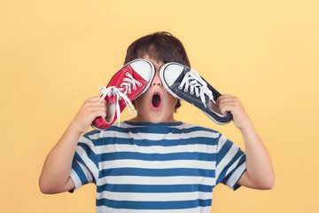 Funny child who covers an eyes with a sneakers