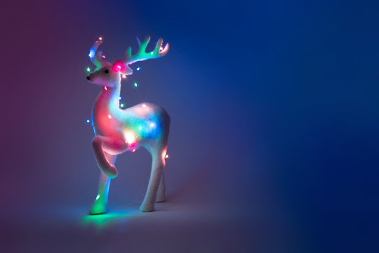 Neon reindeer tree with Christmas lights. Minimal New Year concept.