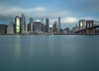 Financial District with Brooklyn bridge from east river at sunrise with long exposure