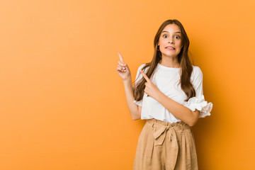 Young caucasian woman shocked pointing with index fingers to a copy space.