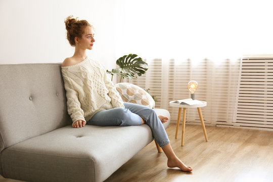 Young beautiful woman wearing white sweater on grey textile sofa at home. Attractive slim female in domestic situation, resting on couch in her lofty apartment. Background, copy space, close up.