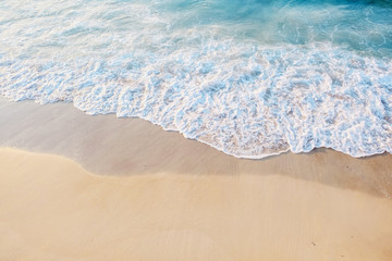 Sea shore close-up. Beautiful blue water with foam near the sandy shore. Place for text. The concept of marine recreation, vacation or tourism. Top view. Wall mural