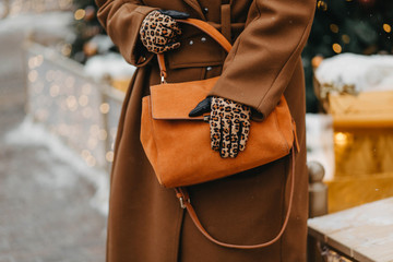 Outdoor fashion portrait of plus size woman wearing trendy animal, leopard print. Concept of autumn and winter clothes, outfit for glamour woman in city. Background of Christmas decorations. Copy
