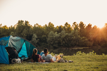 Spoed Foto op Canvas Kamperen young happy couple camping together and relaxing outdoor by the river