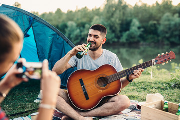 friends on camping playing guitar and taking pictures with smartphone