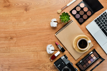 female wooden desktop with Laptop, notepad, Lipstick, powder, comb, women's jewelry. Top view. Free space for your text. Flat lay.