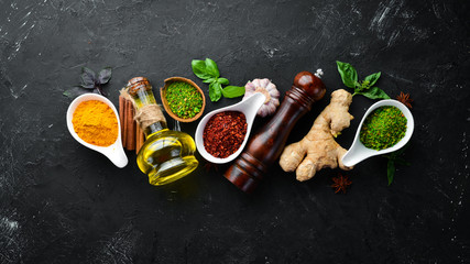 Wall Mural - Colorful herbs and spices for cooking. Indian spices. On a black stone background. Top view.