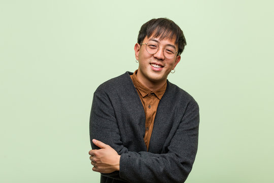 Young chinese man wearing a cool clothes style against a green background