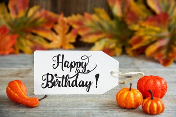 White Label With English Text Happy Birthday. Wooden Background With Autumn Decoration Like Pumpkin And Leaves