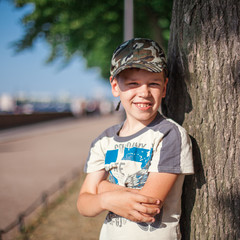 portrait of a boy on the waterfront on a sunny day under the trees