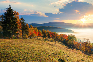 amazing countryside in fall season at sunrise. gorgeous view in to the valley full of glowing fog. sun above the distant mountains. fence through rural field on the hillside. beautiful autumn landscap