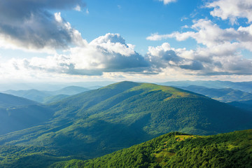 summer afternoon in mountains. wonderful landscape of green carpathian. beautiful fluffy clouds on a blue sky above the ridge. travel freedom concept.