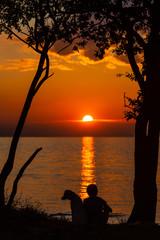 Junge sitzt mit seinem Hund am Meer und sieht dem Sonnenuntergang zu