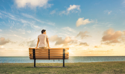 young man sitting on a bench watching the sunrise.  Wall mural