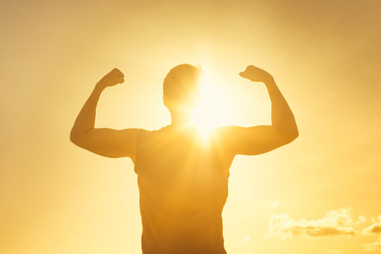 Strong man flexing in the sunshine. Strength, fitness and determination.