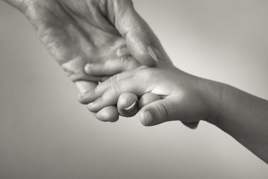 Female hand holding a small Childs hand. Giving love and care to a child concept.