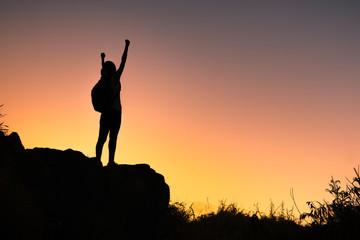 Goal setting. Female climber reaching top of mountain