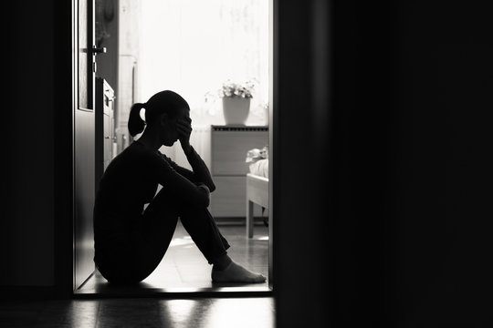 Sad woman sitting alone at home in dark room
