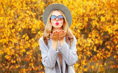 Autumn portrait stylish woman blowing red lips sending sweet air kiss wearing gray coat, round hat on yellow leaves background
