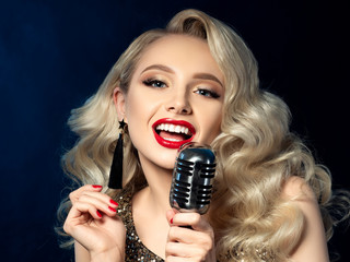 Portrait of pretty blond female singer holding microphone