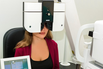 Eyesight measurement of young woman with a optical phoropter