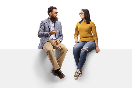 Bearded man talking to a young female seated on a banner