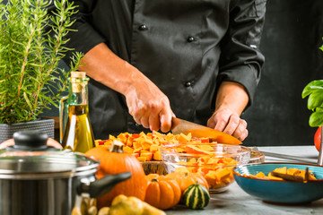 Chef cutting fresh and delicious pumkin and vegetables for cooking soup