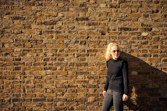 Attractive blonde posing against brick wall