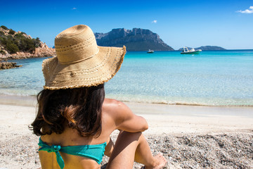 Woman sitting on the doctor's beach in Olbia, in a moment of relaxation, enjoying the view of the crystal clear sea on the north-eastern coast of Sardinia - Olbia / Tempio