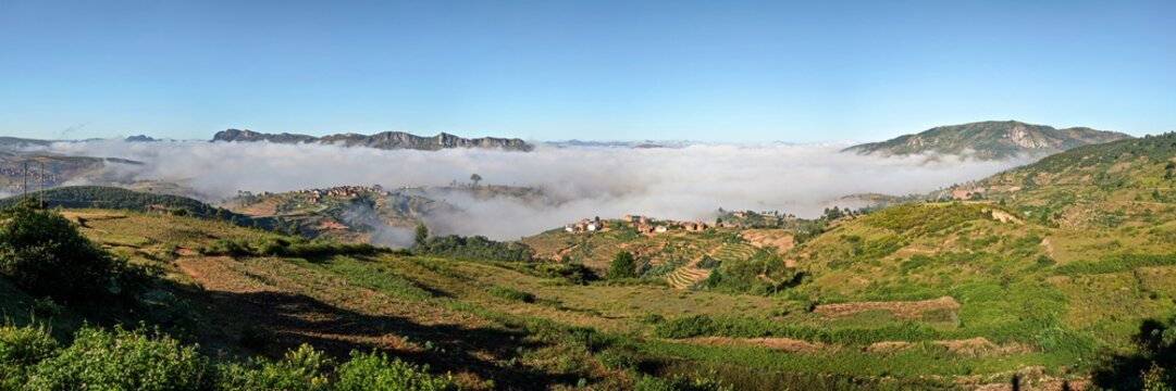 High resolution panorama - typical Madagascar landscape at Alakamisy Ambohimaha region fog rolls over green valley with terraced rice field, clay houses on small hills, higher mountains in background