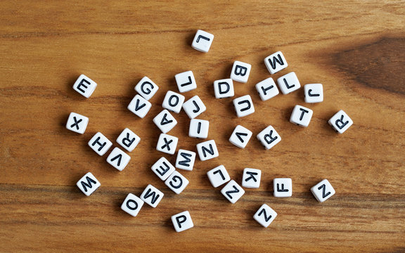 Small white cube beads with various letters scattered on wooden board, view from above