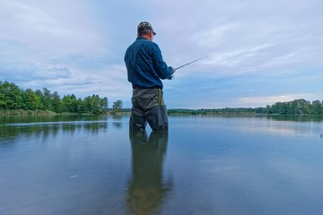 angler standing in the lake during cloudy day