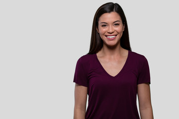 Commercial head shot advertising portrait of a pretty brunette woman with perfect white teeth, smiling with copy space