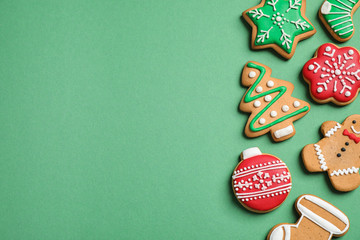 Flat lay composition with tasty homemade Christmas cookies on green background, space for text
