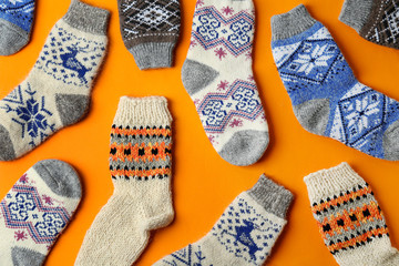 Fototapete - Different knitted socks on orange background, flat lay. Winter clothes