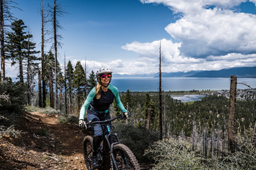 female mountain biker with lake and clouds