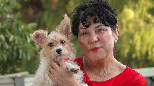 Outdoor portrait of senior Hispanic woman holding her dog