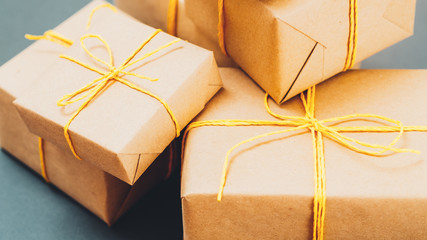 Craft and gift shop. Handmade packaging. Cropped closeup of beige paper boxes stack on blue sage background.
