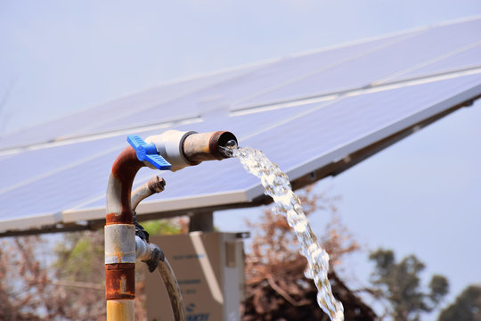 agricultural equipment for field irrigation, water jet, behind which is solar panel's.