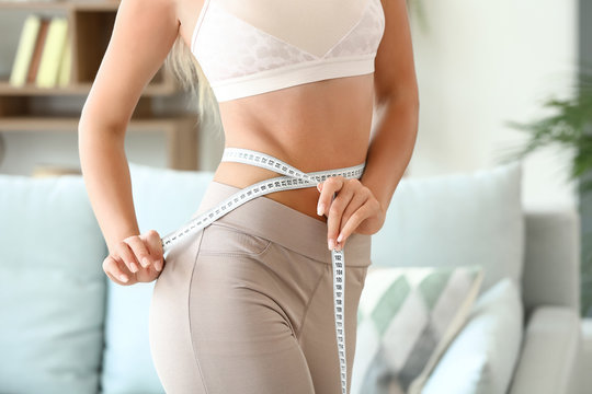 Beautiful young woman with measuring tape at home. Weight loss concept