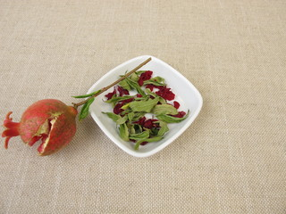 A small pomegranate, pomegranate leaves and pomegranate blossoms in a bowl