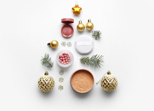 Christmas composition with decorative cosmetics on white background
