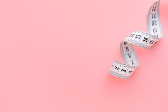 Measuring tape on color background