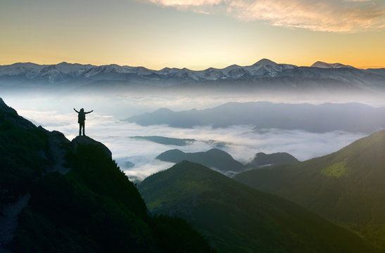 Wide mountain panorama. Small silhouette of tourist with backpack on rocky mountain slope with raised hands over valley covered with white puffy clouds. Beauty of nature, tourism and traveling concept