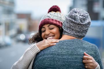 Multiethnic couple hugging outdoor in winter