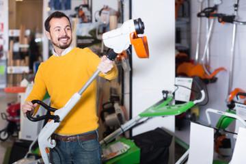 Smiling guy deciding on best manual lawnmower in garden equipment shop