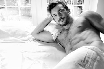 Handsome hairy naked muscular man with beard sixpack abs lying in bed covered with sheet