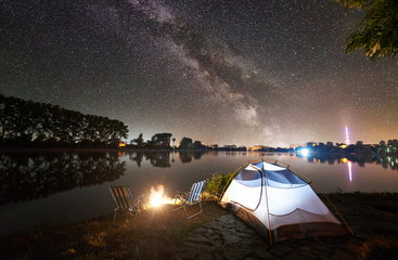 Night camping under starry sky. Glowing tourist tent, two chairs and bonfire on lake shore under beautiful evening sky full of stars and Milky way, city lights on background. Outdoor lifestyle concept