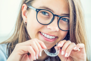 Dental invisible braces or silicone trainer in the hands of a young smiling girl. Orthodontic concept - Invisalign