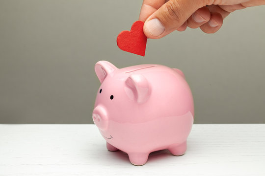 Donations of love and feelings, sympathy. Man puts heart in piggy bank